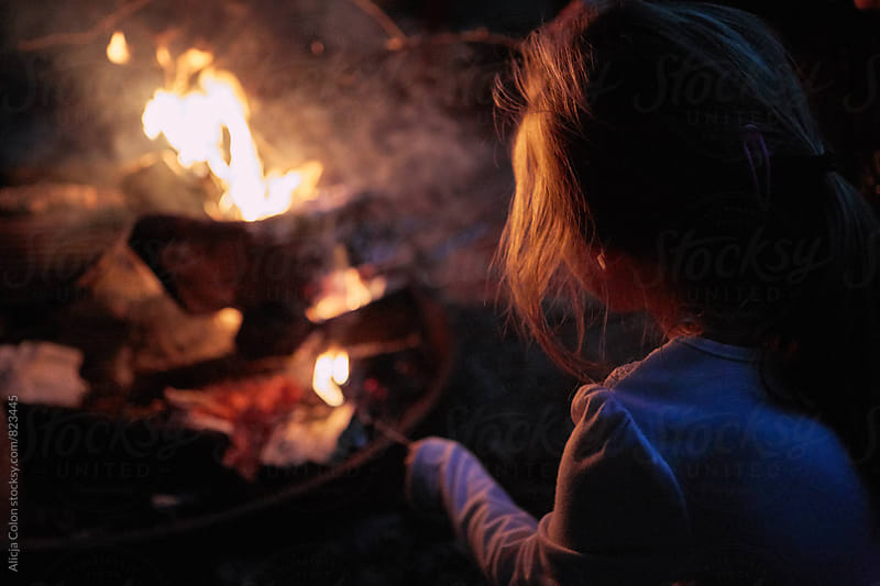 Young girl gazing at campfire by Alicja Colon for Stocksy United