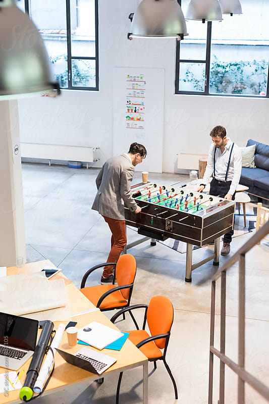 Businessmen playing table-football in a cool office by GIC for Stocksy United