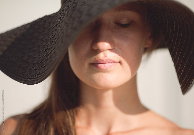 portrait of the young woman with black hat,natural light  by Alexey Kuzma for Stocksy United