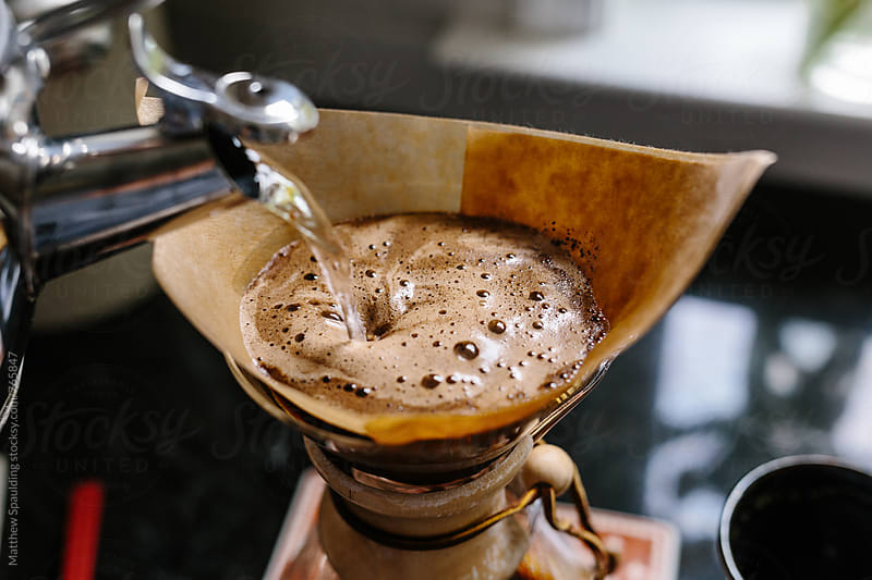 Pouring hot water over fresh coffee grounds by Matthew Spaulding for Stocksy United