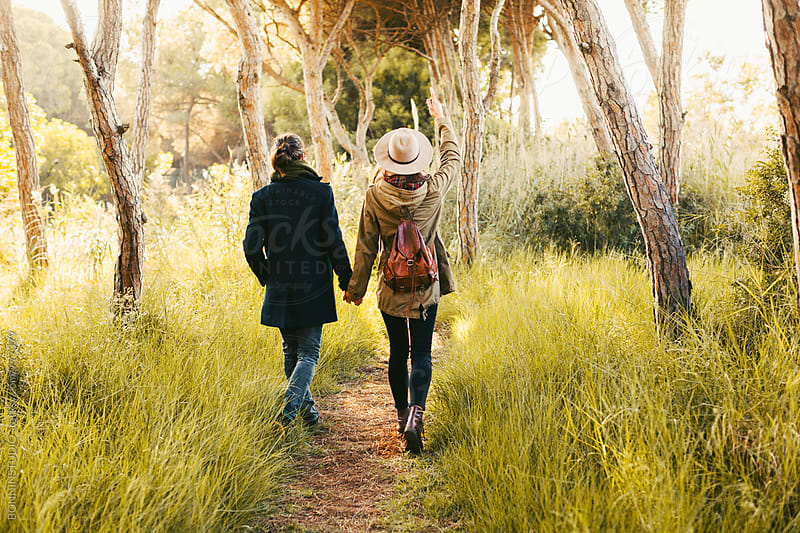 Back view of a hipster couple walking in the forest. by BONNINSTUDIO for Stocksy United
