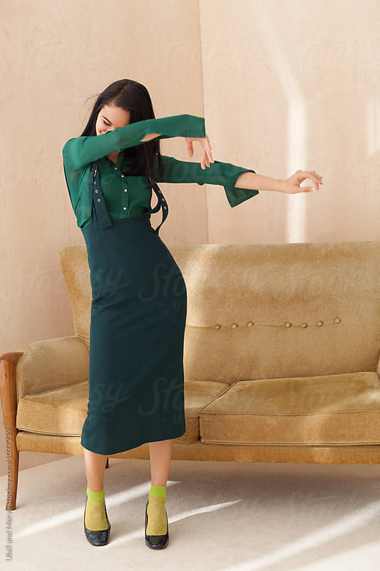 happy young woman wearing a green dress dancing by Ulaş and Merve for Stocksy United