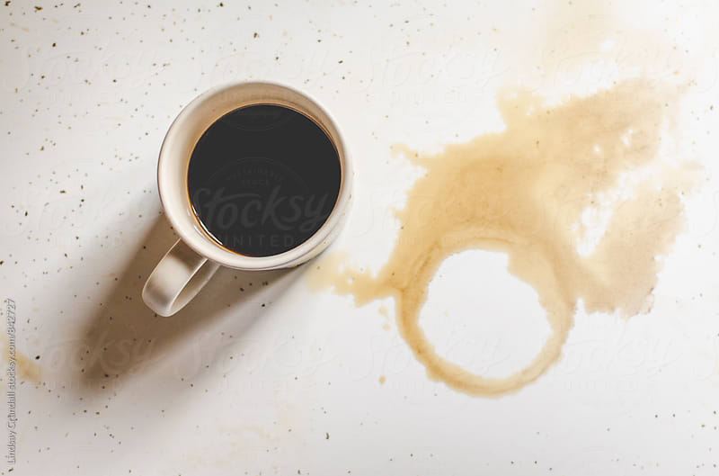 Black coffee in mug next to spilled coffee by Lindsay Crandall for Stocksy United