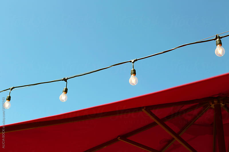 A Red Beach Umbrella With A String Of Lights  by ALICIA BOCK for Stocksy United
