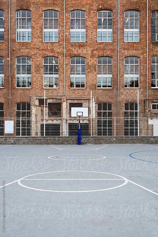 Basketball court with old factory facade behind by Guille Faingold for Stocksy United
