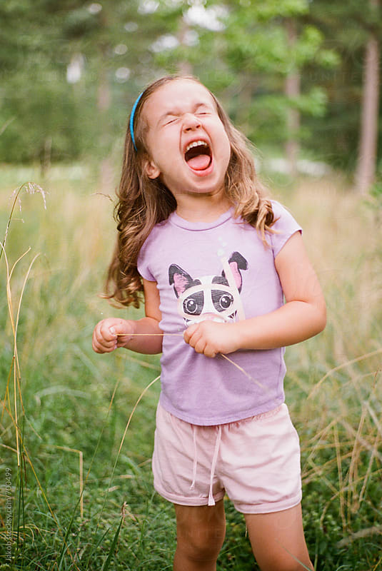 Cute young girl making a funny face in a field by Jakob for Stocksy United
