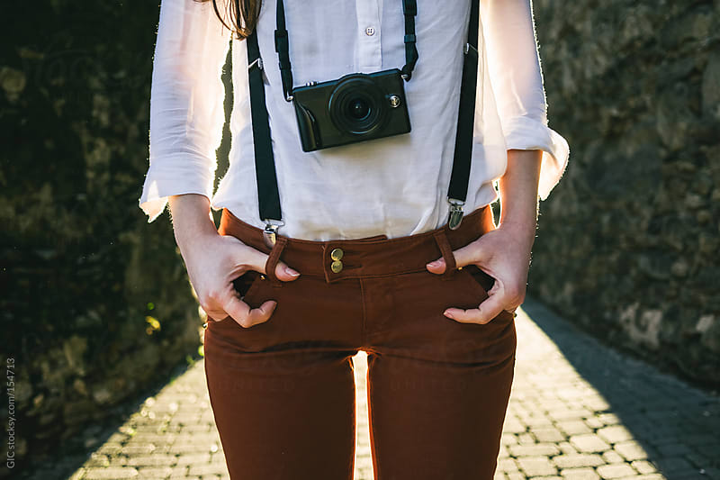 Young cool woman with suspenders and old camera by GIC for Stocksy United