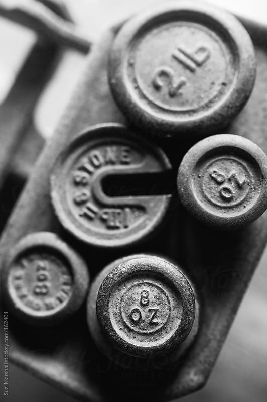 Cast iron weights on antique metal scales by Suzi Marshall for Stocksy United