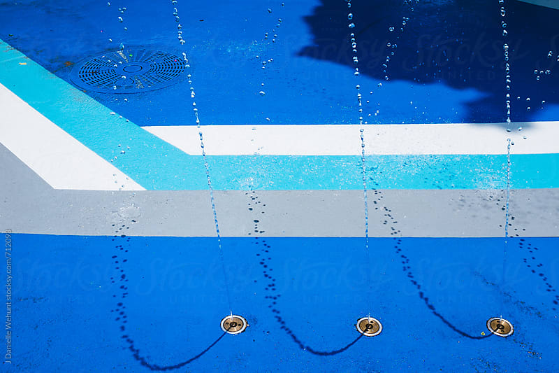 A view from above of a blue splash pad with strong modern lines. by J Danielle Wehunt for Stocksy United