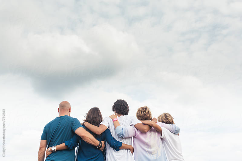 Upper body shot from the back of a family with their arms around each other by Cindy Prins for Stocksy United