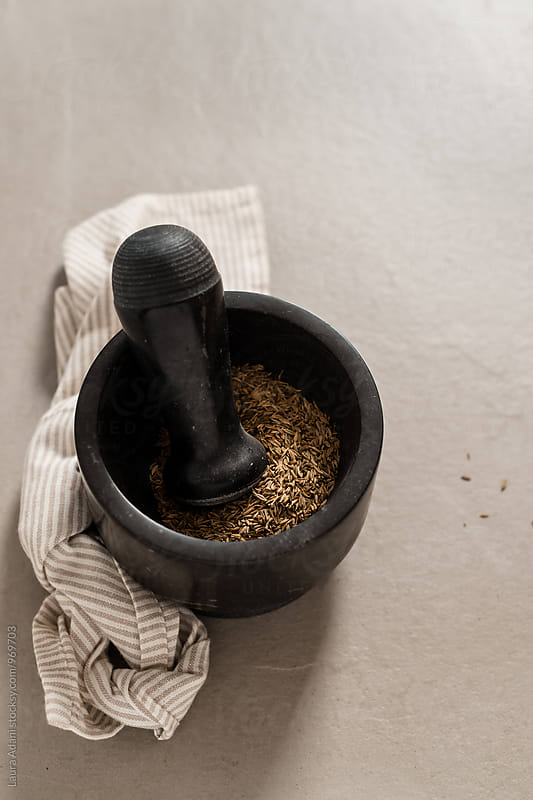 A pestle and mortar with cumin seeds by Laura Adani for Stocksy United