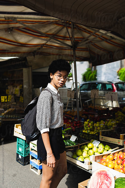 Young woman at the local vegetable market by michela ravasio for Stocksy United