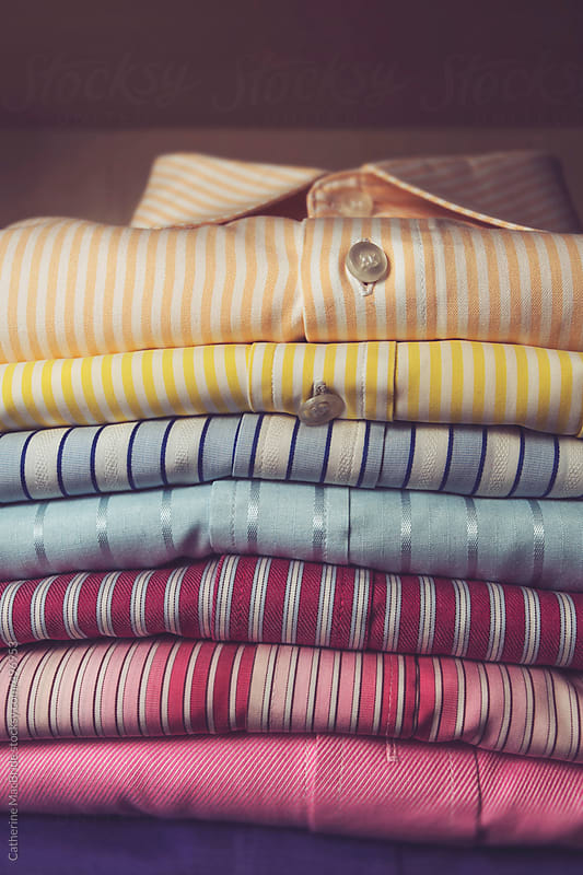 A stack of folded mens shirts... by Catherine MacBride for Stocksy United