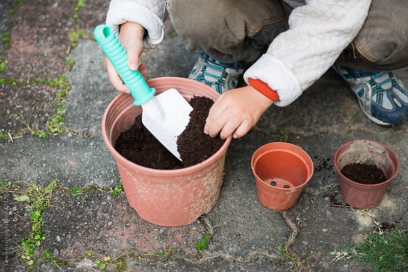 Young Kid in Hooded Jacket Planting Something on Pot Outside by Lawren Lu for Stocksy United
