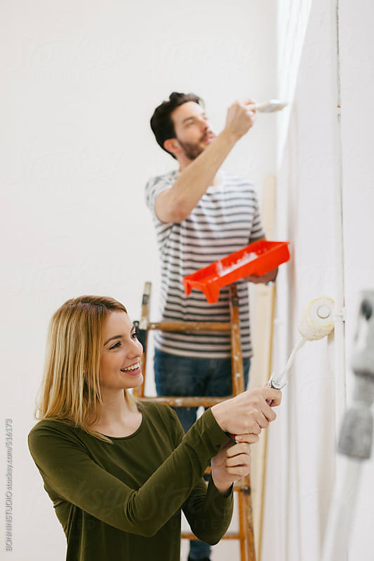 Young couple painting white wall for their new home.  by BONNINSTUDIO for Stocksy United
