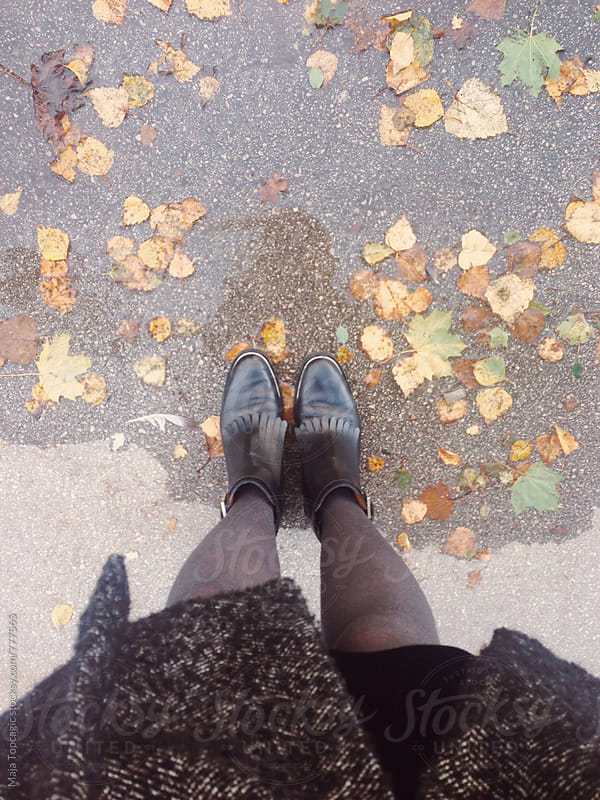Female boots stading near a pond of rain with autumn leaves by Maja Topcagic for Stocksy United