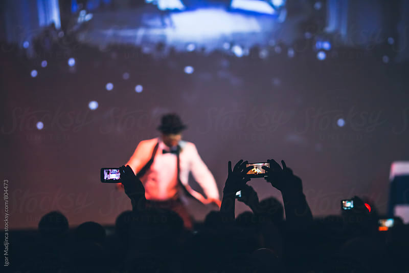 audience with mobile phones,stage,dancer by Igor Madjinca for Stocksy United