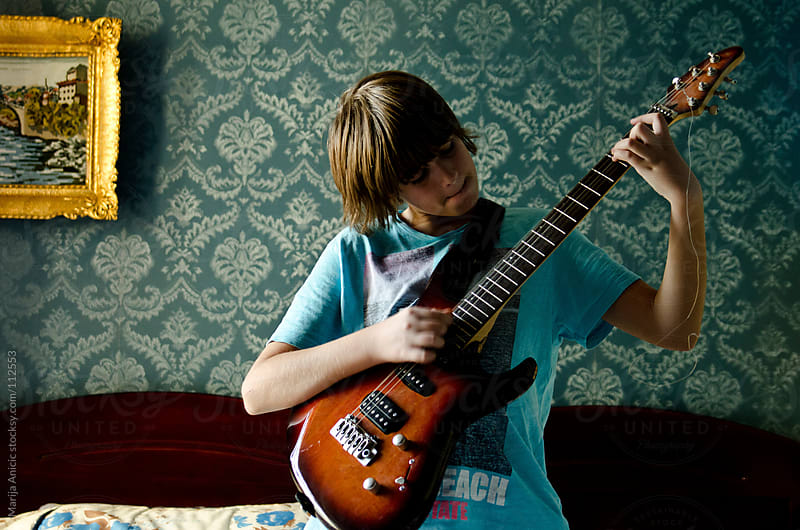 Boy is playing electric guitar in retro room of his parents by Marija Anicic for Stocksy United