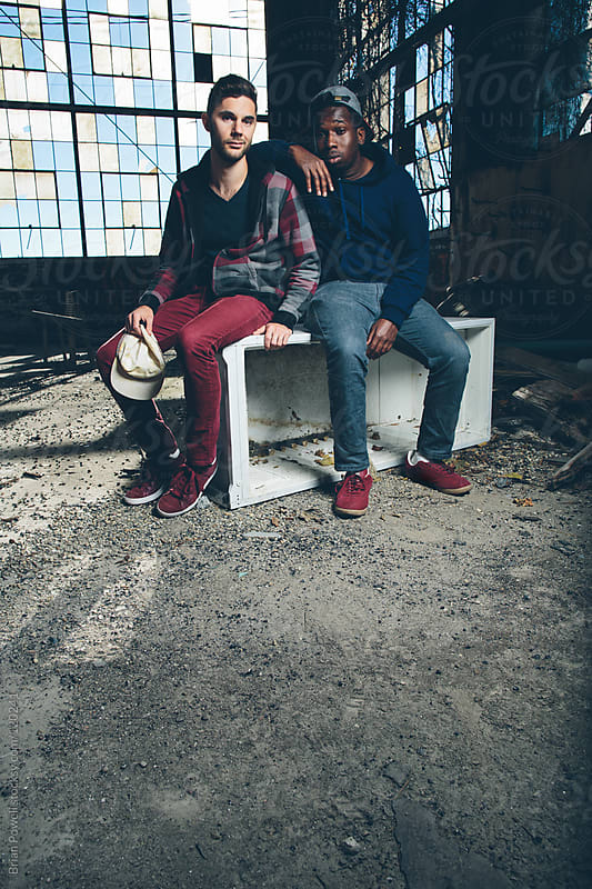 two cool guys sitting in warehouse by Brian Powell for Stocksy United