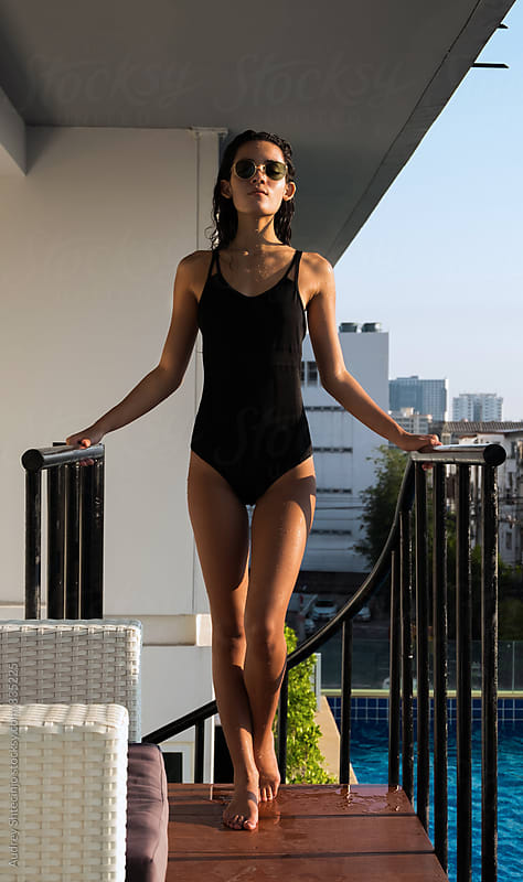 Attractive stylish young female in black tricot standing on sun on balcony with city in background. by Marko Milanovic for Stocksy United