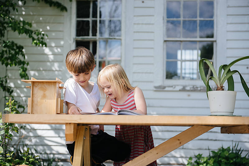 Two children read a book together outside in summer by Cara Dolan for Stocksy United