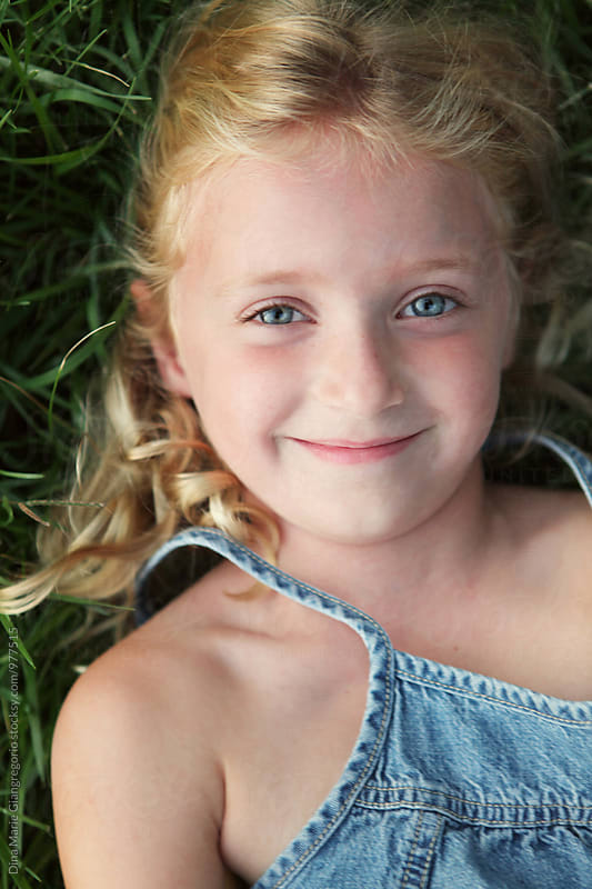 Content Little Blonde Girl Laying in Grass Smiling by Dina Giangregorio for Stocksy United