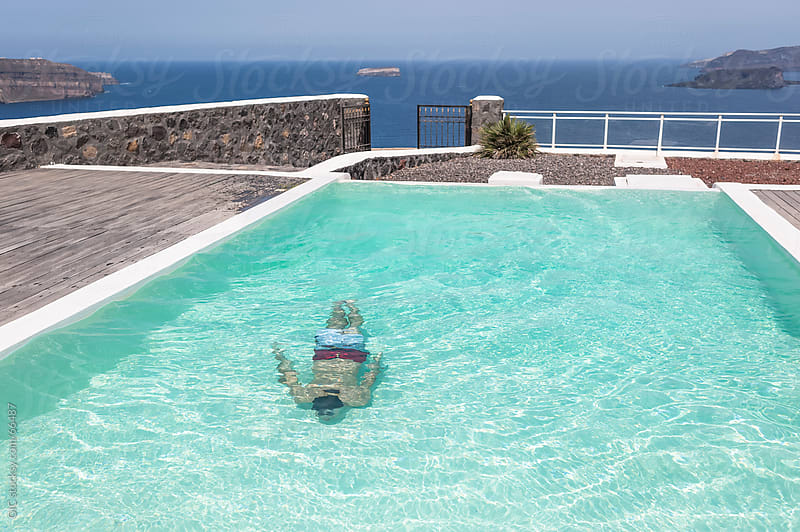 Man in swimming pool in Santorini by GIC for Stocksy United