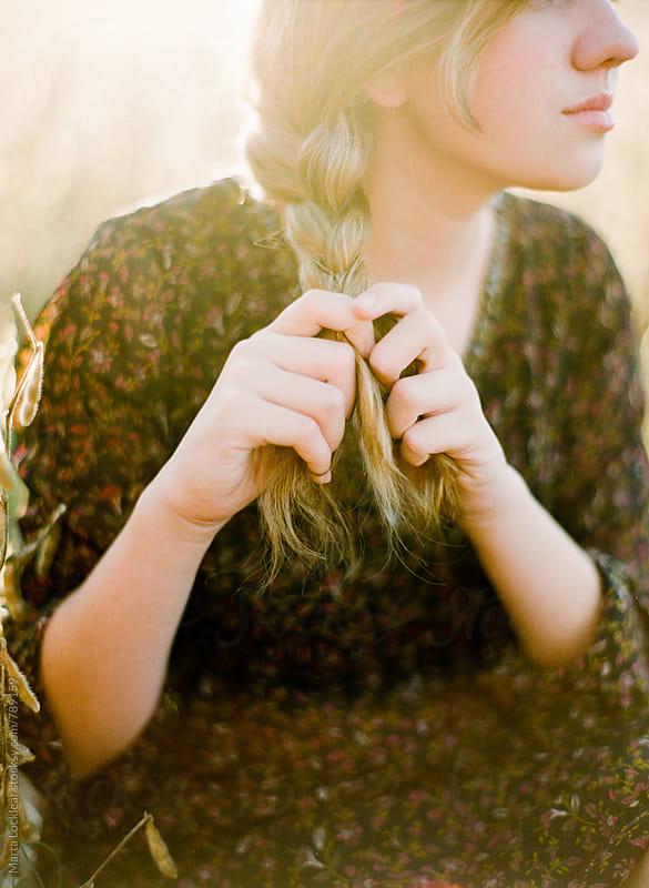 Teen braiding her hair  by Marta Locklear for Stocksy United