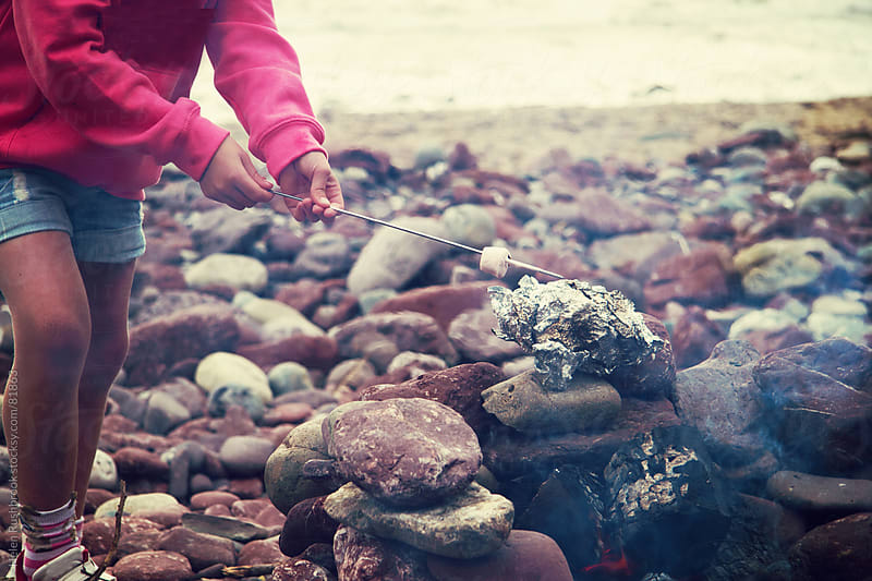 A little girl toasting marshmallows over a fire on a beach. by Helen Rushbrook for Stocksy United