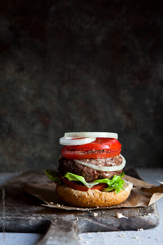 Juicy beef burger with tomato, lettace and onion by Nadine Greeff for Stocksy United
