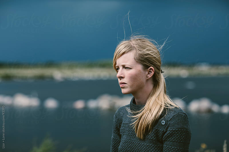 Portrait of young blond woman by the sea by Lior + Lone for Stocksy United
