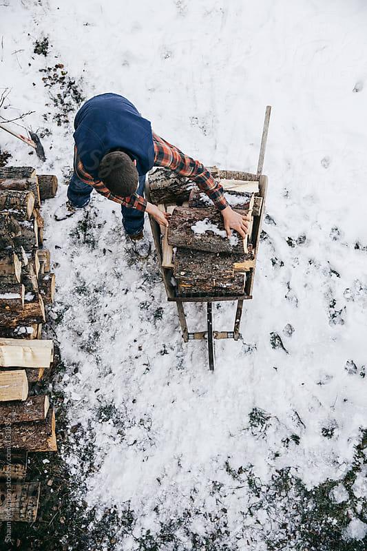 man loading wood into a wheelbarrow  by Shaun Robinson for Stocksy United