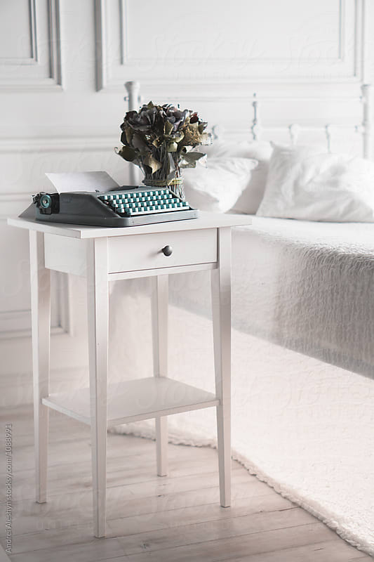 white room with a bed and a cupboard with a typewriter by Andrei Aleshyn for Stocksy United