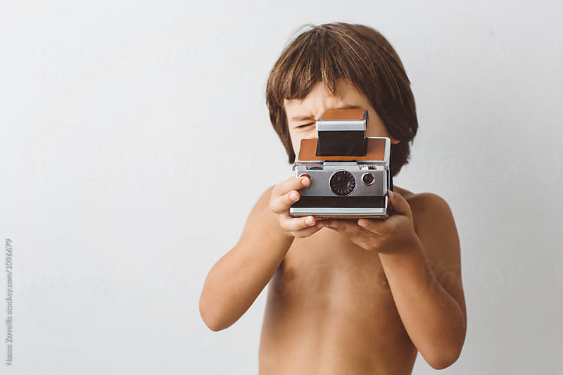 5 year old boy holding an instant camera by Nasos Zovoilis for Stocksy United