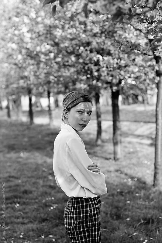 Black and white photo of a girl standing in park by Hamza Kulenović for Stocksy United