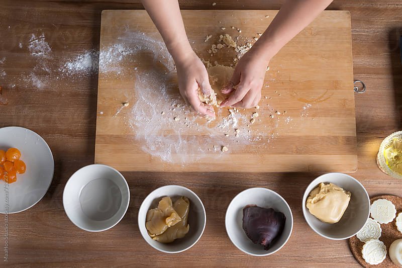 A young Chinese woman kneading dough by MaaHoo Studio for Stocksy United