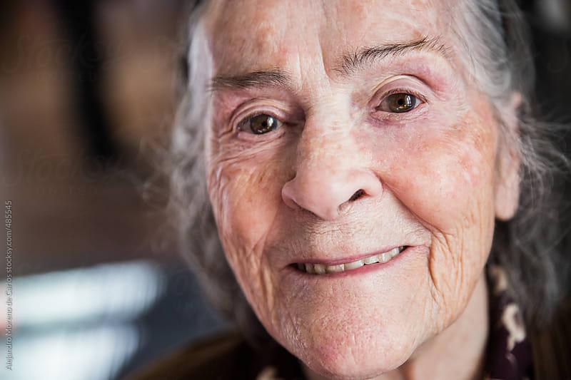 Senior woman smiling portrait looking at camera by Alejandro Moreno de Carlos for Stocksy United