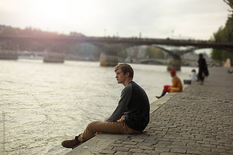 Boy sitting on the quay of the Seine by Marcel for Stocksy United