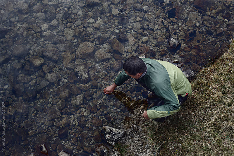 Young man touching the water and rocks of a mountain stream by Miquel Llonch for Stocksy United