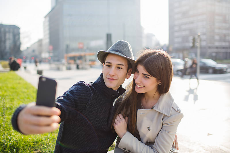 Smiling couple taking a selfie in the city by michela ravasio for Stocksy United