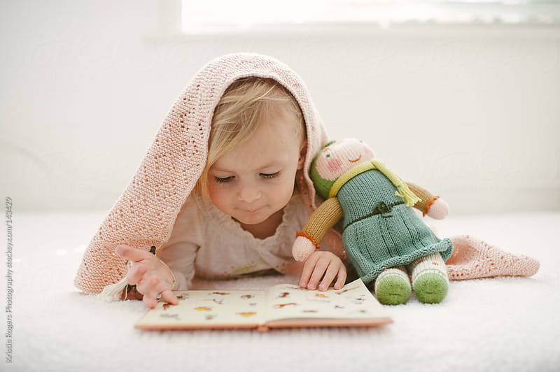 cute girl toddler on bed looking at book with doll and blanket by Kristin Rogers Photography for Stocksy United