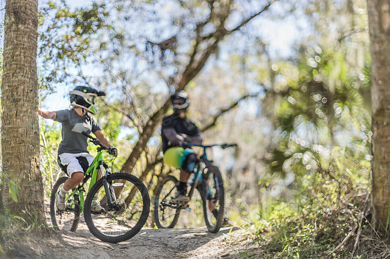 Two Friends Mountain Biking Resting Between Jumps by suzanne clements for Stocksy United