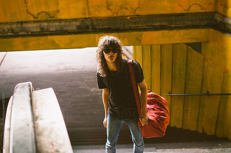 Young man with red traveling bag by Brkati Krokodil for Stocksy United