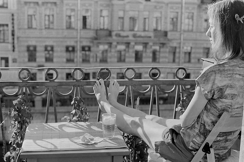 Young woman having breakfast on a balcony by Lyuba Burakova for Stocksy United