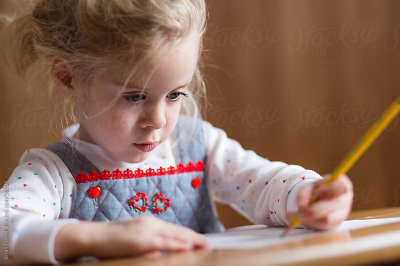 preschool girl writes at desk by Brian Powell for Stocksy United
