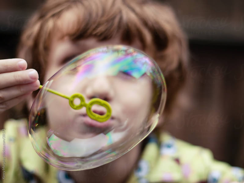 Young boy at play blowing bubble by Kerry Murphy for Stocksy United