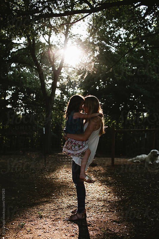 mother and daughter at sunset by Erin Drago for Stocksy United