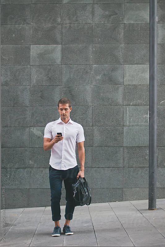 Casual businessman sending text message with phone on the street. by BONNINSTUDIO for Stocksy United