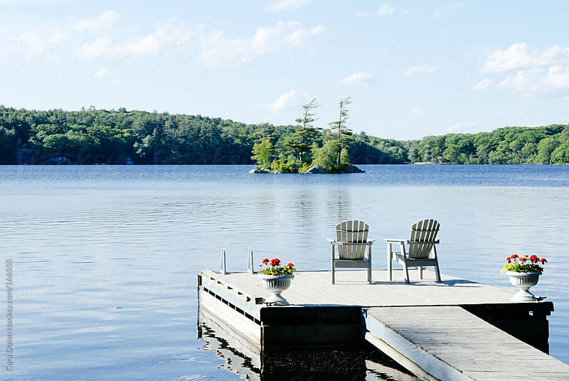 Dock floating in a lake on a beautiful summer day by Cara Dolan for Stocksy United