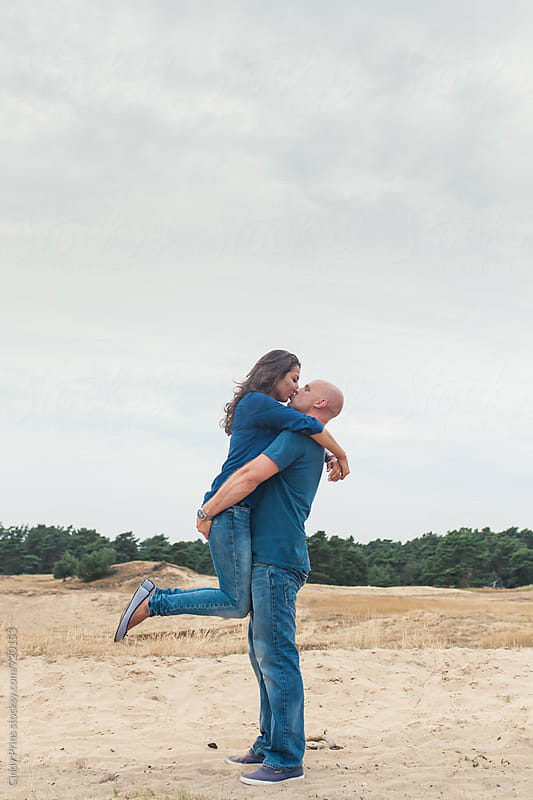 Man picking woman up from the ground for a kiss by Cindy Prins for Stocksy United